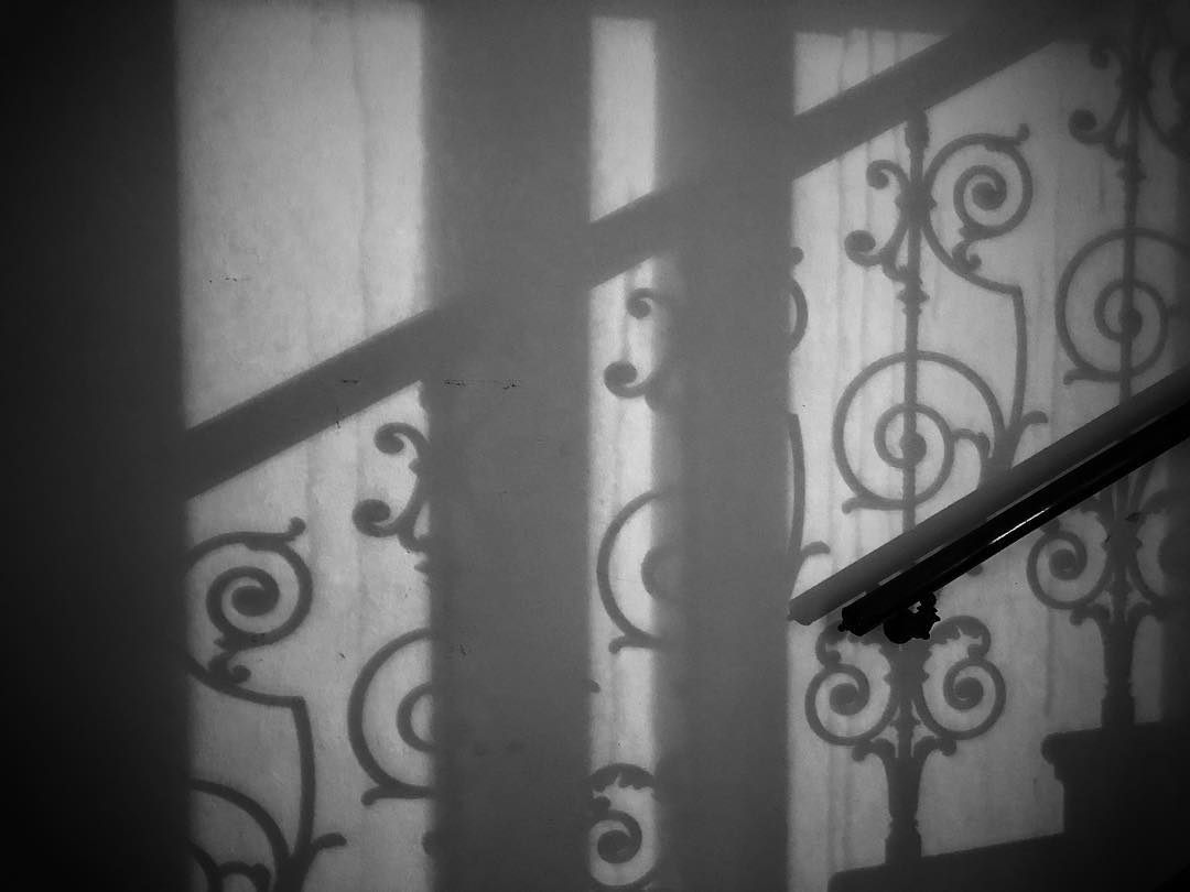 Banister alongside a staircase shadow
